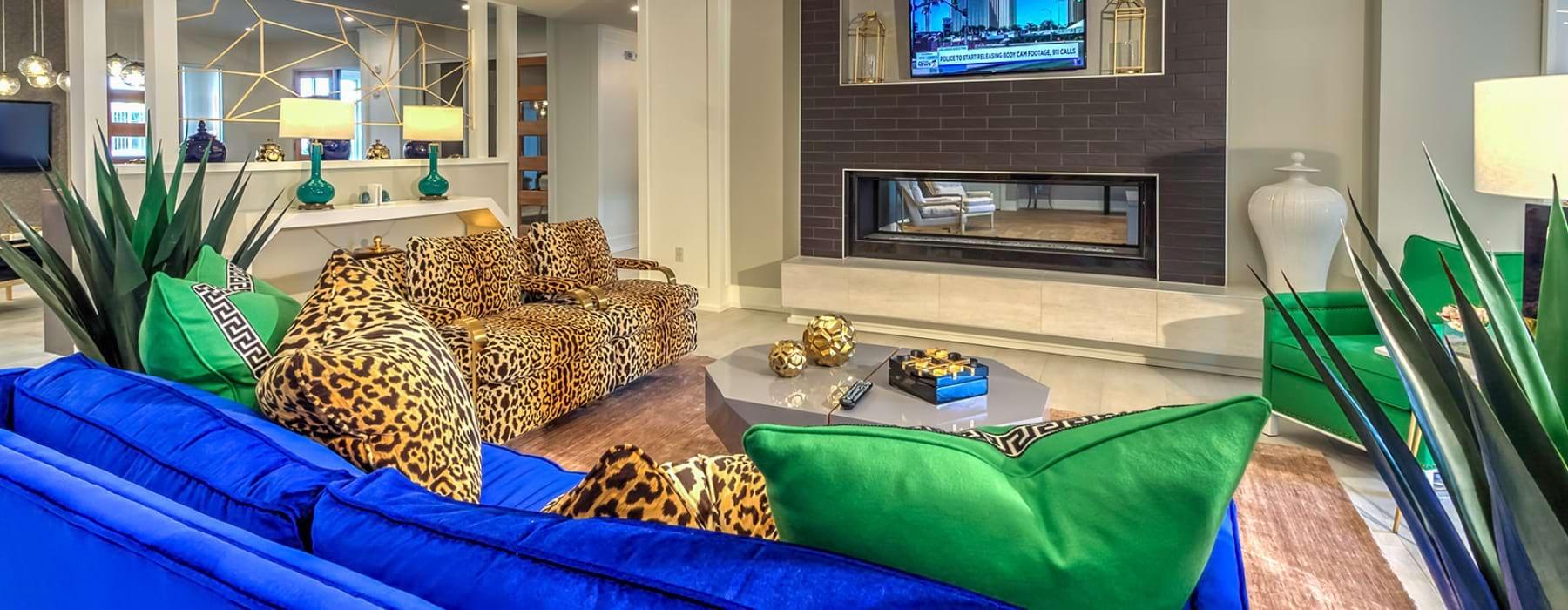 Asientos de sofá de la casa club con televisión colgante y chimenea.